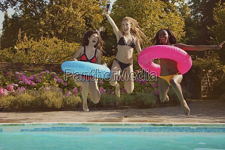 playful teenage girl friends jumping into