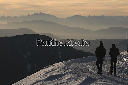 silhouetted people hiking on snowy mountain