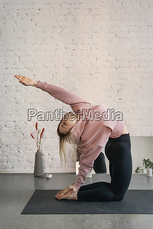young woman practicing camel pose backbend