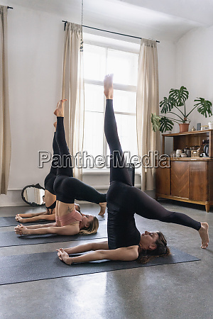young women practicing yoga in yoga