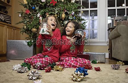 glueckliche schwestern im pyjama mit schneekugeln