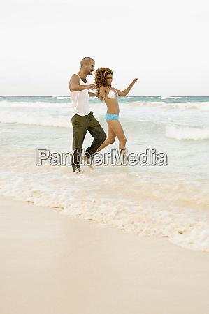 paar spielt in wellen am strand