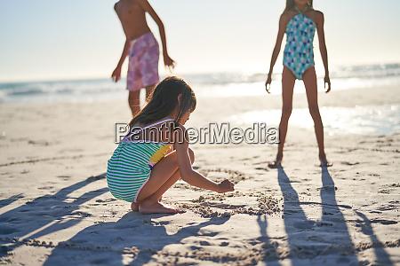 maedchen ziehen herz im sand am
