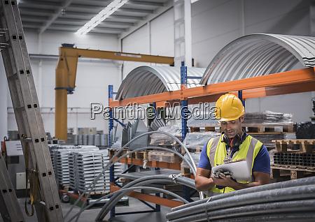 maennlicher supervisor mit zwischenablage in stahlfabrik
