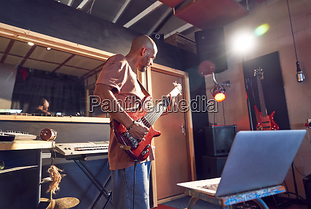 male musician practicing guitar at laptop