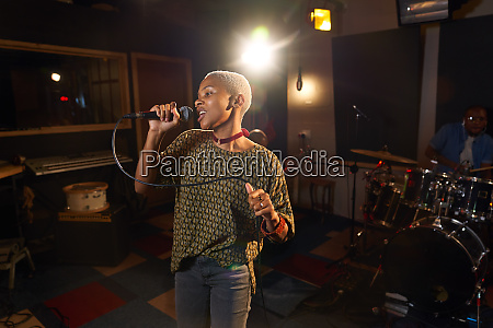 female musician singing into microphone in