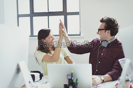 computer programmers high fiving at laptop