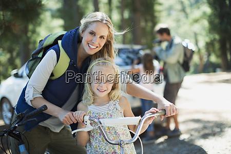 laechelnde mutter und tochter mit fahrrad