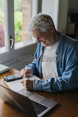 gluecklicher senior mann auf papier schreiben