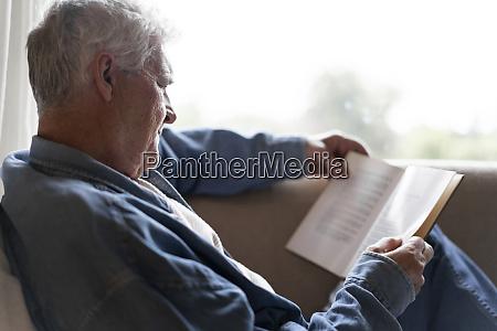 senior mann lesen buch beim entspannen