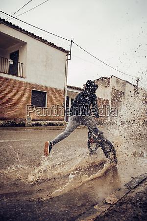 teenager, der, wasser, in, pfützen, während, er, auf - 28737264