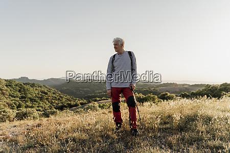 senior maennlich wanderer blickweg waehrend stehend