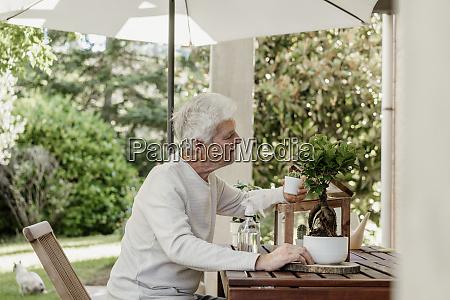 senior mann mit hauspflanzen auf terrasse