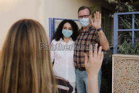paar traegt masken winken haende zu