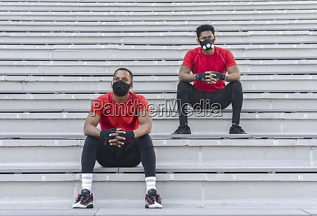 zwei sportler mit masken sitzend auf
