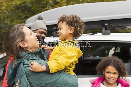 glueckliche familie umarmt vor dem auto