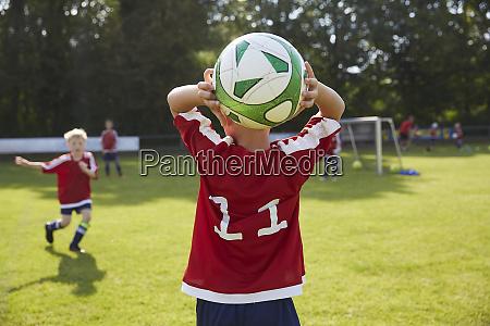 fussballjunge wirft ball auffeld