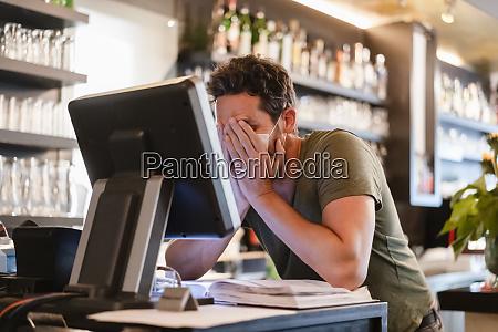 restaurantleiter mit haenden im gesicht waehrend