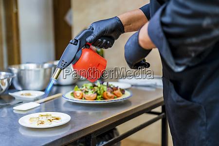 chef bereitet dessert mit broetchenbrenner zu