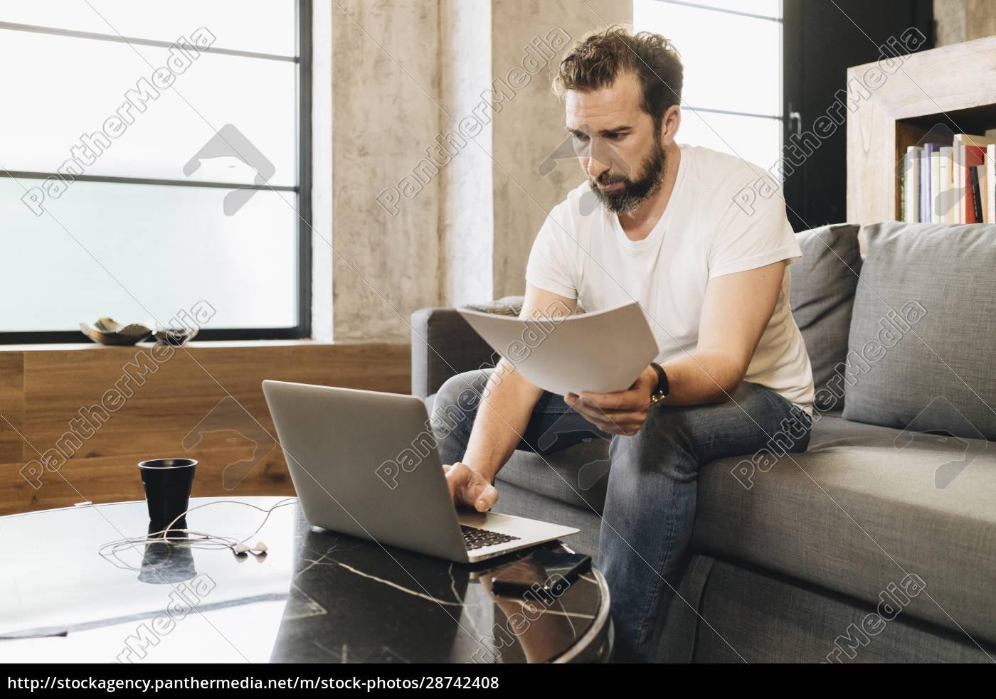 reifer, mann, der, auf, der, couch, sitzt, laptop - 28742408