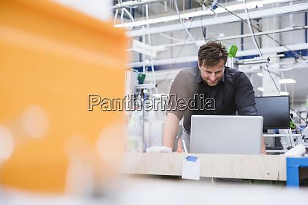 mann mit laptop in der fabrik