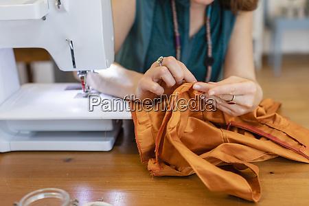 female, seamstress, sewing, orange, fabric, at - 28745126