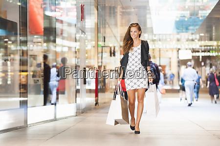 portraet einer gluecklichen frau auf einkaufstour
