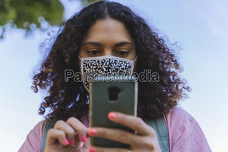 reife frau mit smartphone waehrend pandemie