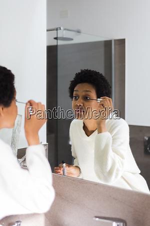 spiegelbild der jungen frau die mascara