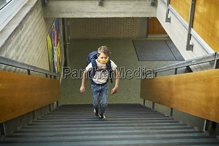 junge traegt maske in der schule