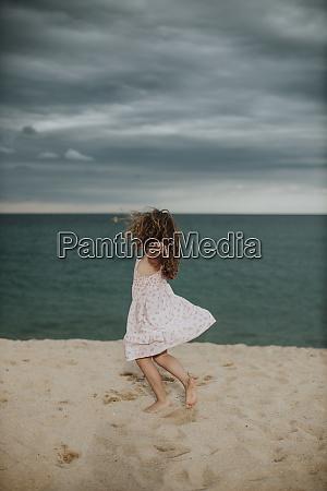 unbekuemmerte maedchen tanzen auf sand gegen