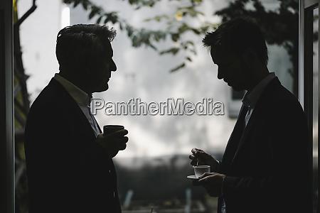 silhouette von zwei geschaeftsleuten die gemeinsam