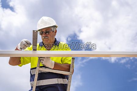 senior maennlicher techniker misst dach waehrend