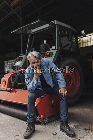 laechelnder senior auf einem bauernhof sitzt