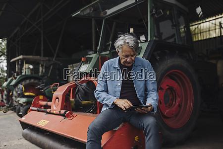 AElterer mann mit tablet auf einem