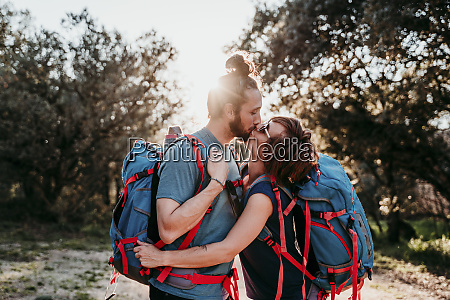 couple, with, backpacks, kissing, on, a - 28748150