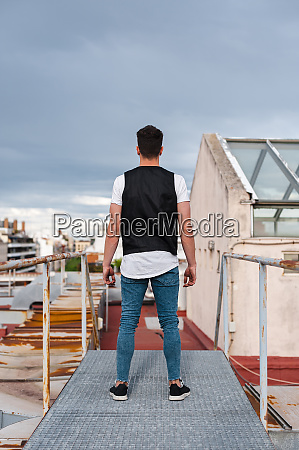 junger mann steht auf verlassener terrasse