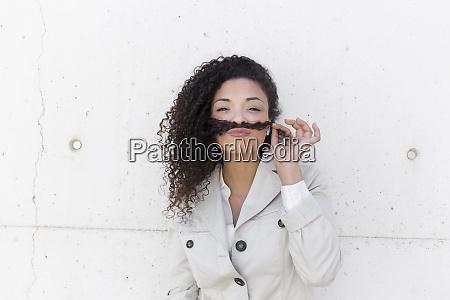 stilvolle geschaeftsfrau haelt haare auf denlippen