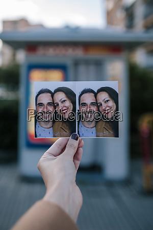 frau hand halten foto vor fotokabine