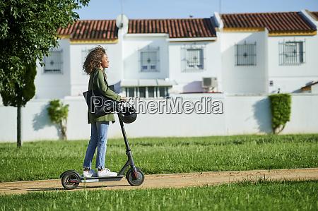 junge frau faehrt elektro push scooter