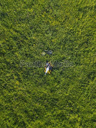 frau auf gras liegend luftbild