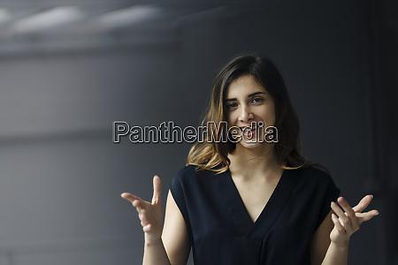 portraet einer gestikulierenden jungen geschaeftsfrau vor