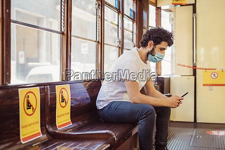 mann traegt gesichtsmaske mit handy waehrend