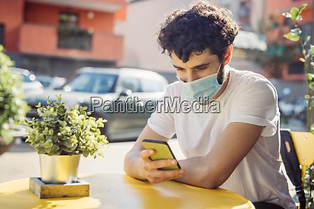 junger mann traegt gesichtsmaske mit smartphone