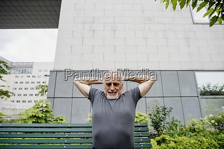 senior mann mit erhobenen armen uebt