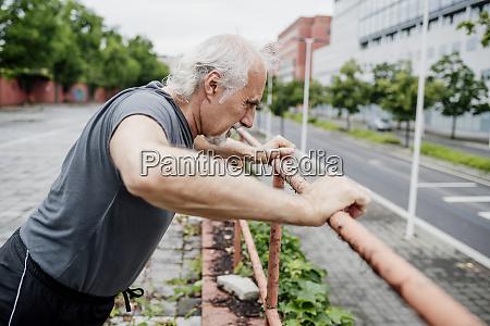 senior mann trainiert auf gelaender in