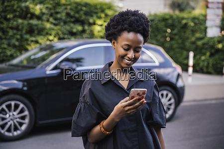 frau mit smartphone vor geparktem auto