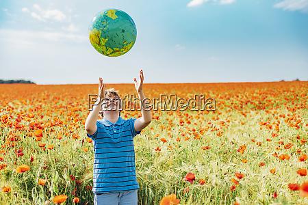 gluecklicher junge faengt globus waehrend er