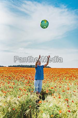 junge faengt globus waehrend im mohnfeld