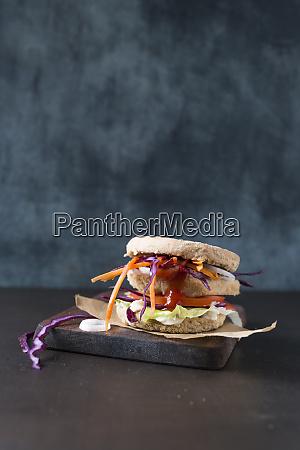 vegetarischer burger mit rotkohlstreifen und tofuschnitzel
